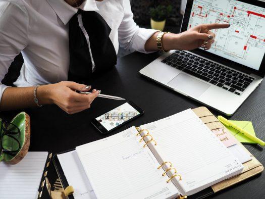 En ejendomsmægler sidder ved sit skrivebord og peger på computeren